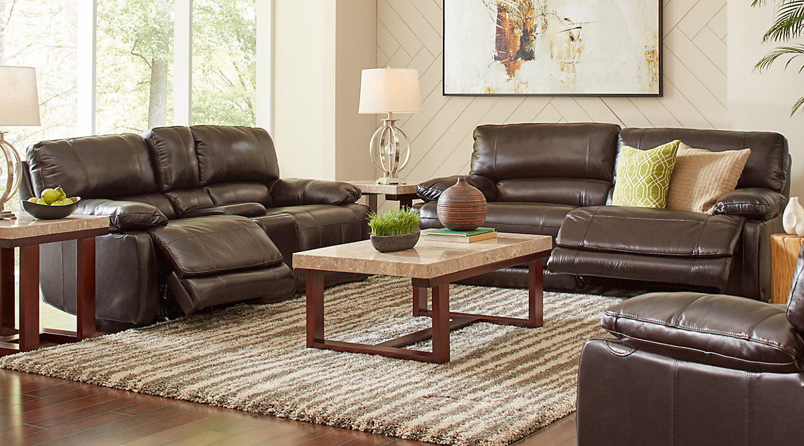 Reclining brown leather couch set with green and beige accent pillows, wooden marble-topped tables on a beige and brown shag rug.
