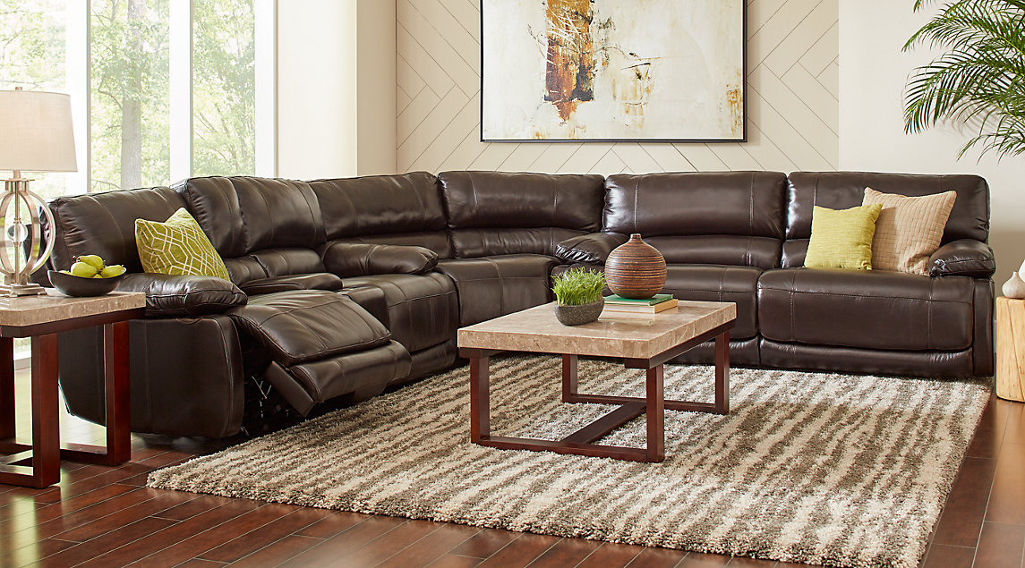 Reclining brown leather couch set with green and beige pillows, wooden marble topped tables on a beige shag rug