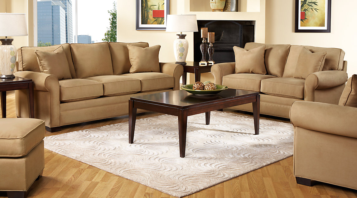 Light brown couch set accented with dark brown tables with green bowls and lamps on a beige rug.