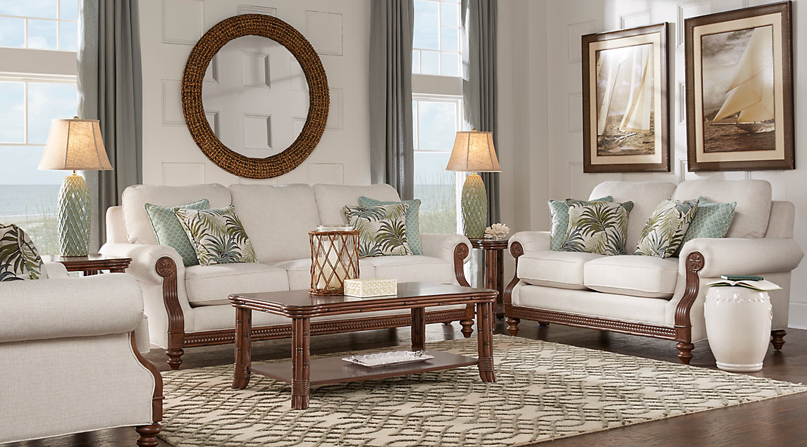 Biege couch set with detailed hand carved rattan armrests, green bamboo printed pillows, and matching wooden tables.