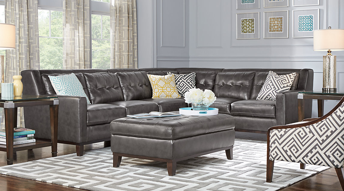 Gray leather sectional with tufted cushions with blue and yellow accent pillows, blue and yellow wall art and a gray rug.