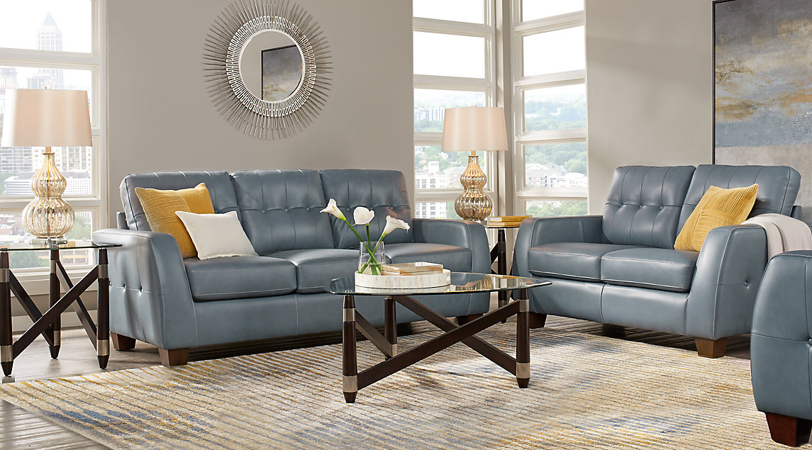 Blue leather sofa set with yellow accent pillows, gray and blue wall art, and a gray, blue and yellow rug.