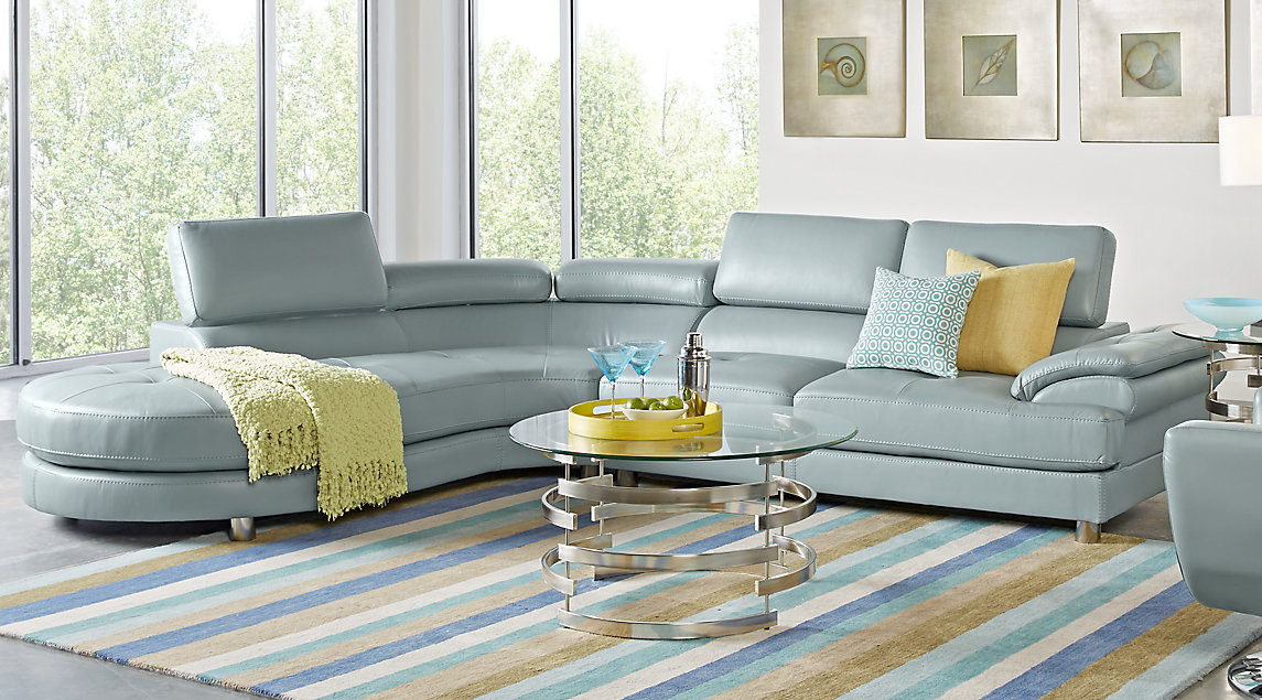 Blue modern sectional with yellow and blue accent pillows, gray metal coffee table, gray wall art, and a blue and gray striped rug.