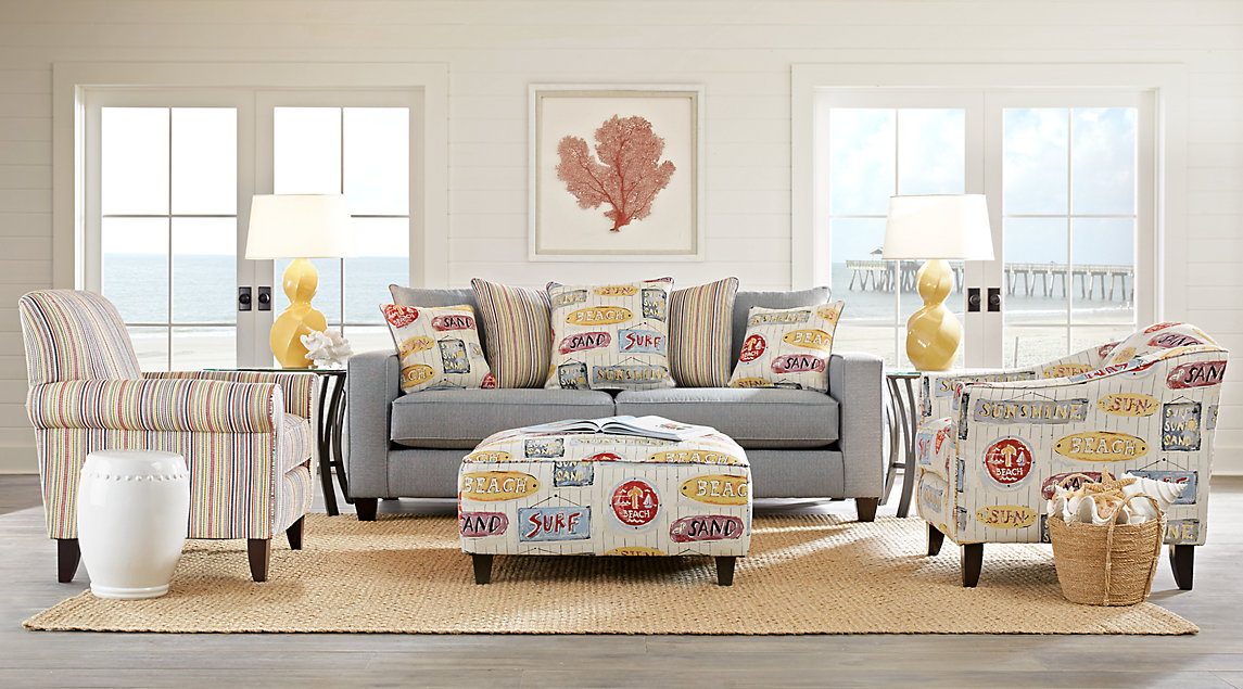 Gray & multi-colored coastal style sofa set including blue tones accented with yellow lamps.