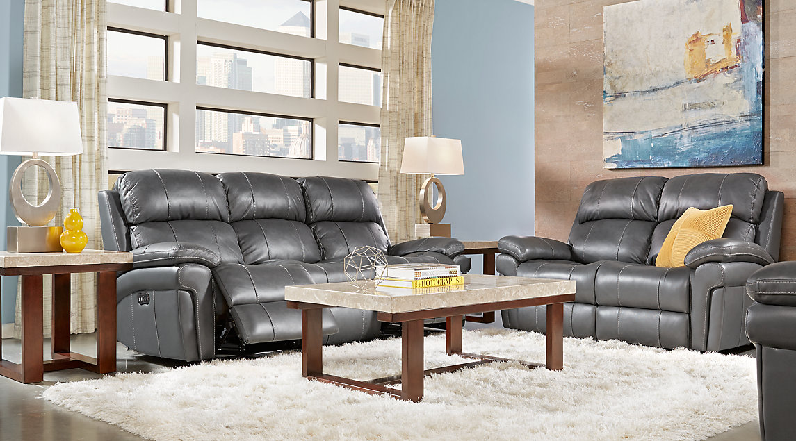 Smoke gray leather reclining sofa set with yellow accent pillows, brown marble-topped end tables and blue and yellow wall art.