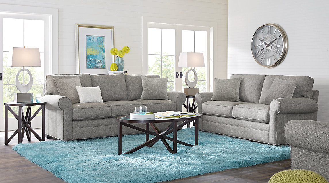 Slate gray sofa set with gray and white pillows, white lamps and a blue shag rug.