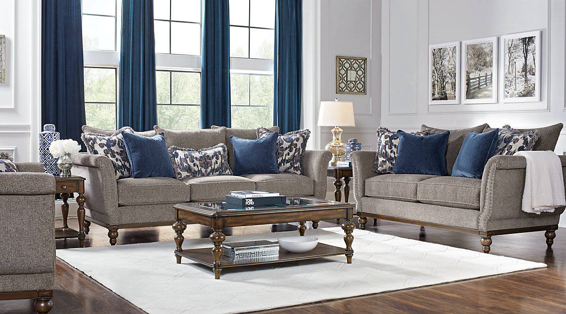 Slate gray sofa set with blue and gray accent pillows, white rug and dark blue curtains.