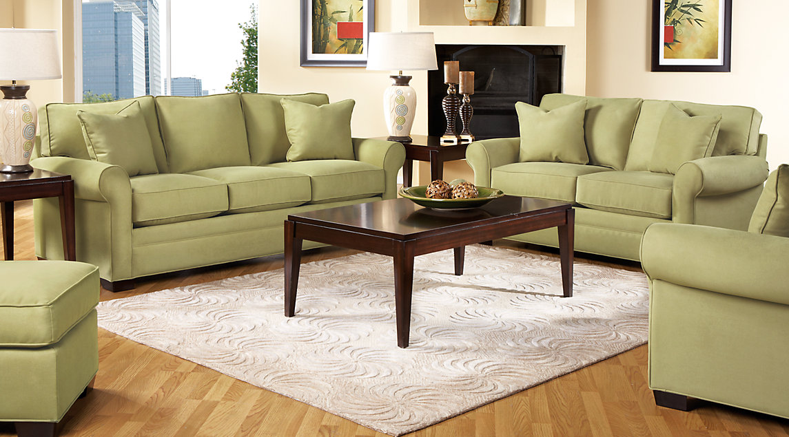 Green couch set accented with dark brown tables, on a beige throw rug.