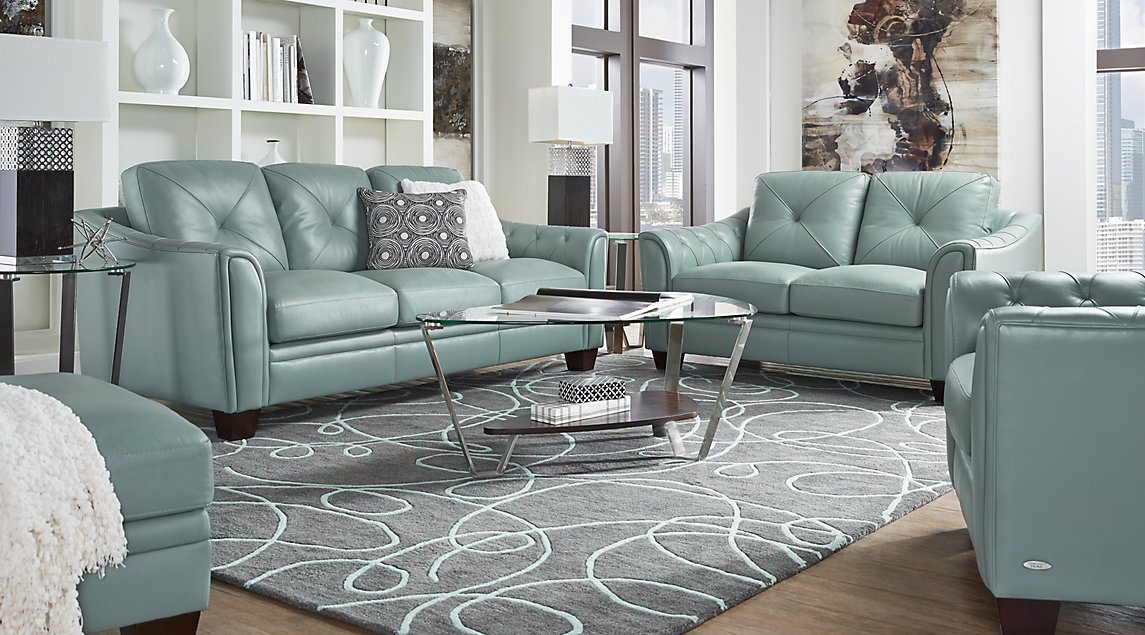 Aqua blue leather sofa set with white and gray accent pillows, white lamps, and a slate gray and blue rug.