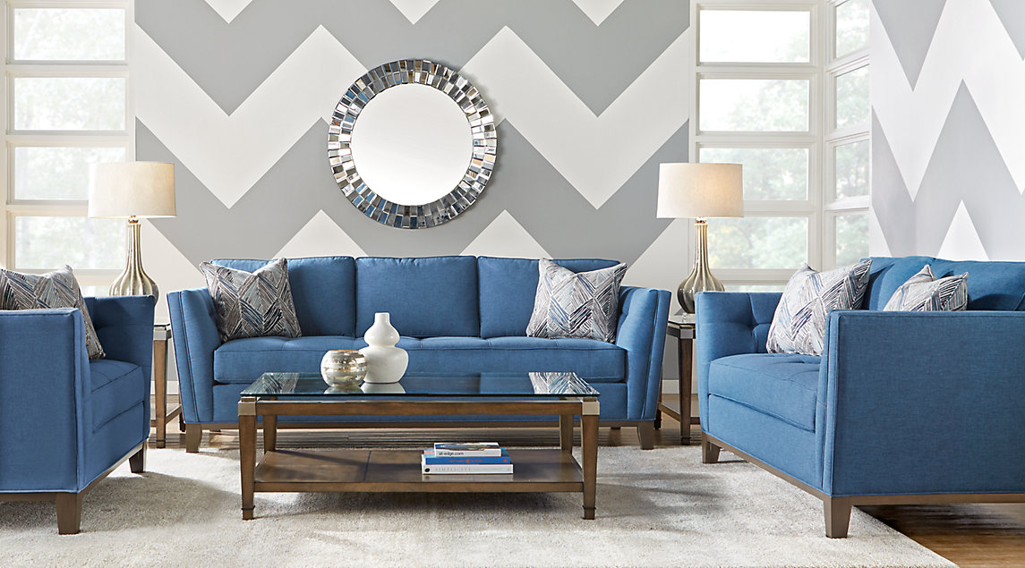 Blue sofa set with blue, white, and slate accent pillows and a white rug.