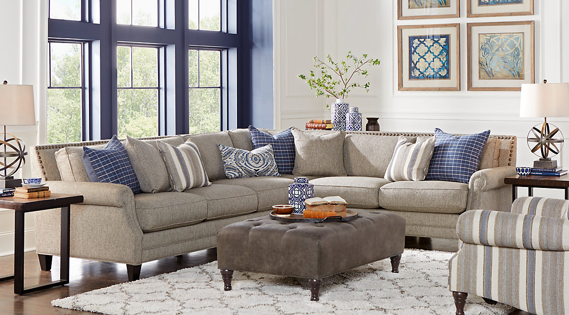Gray sectional with bold nailhead accents, blue and white pillows, tufted gray ottoman, white rug.