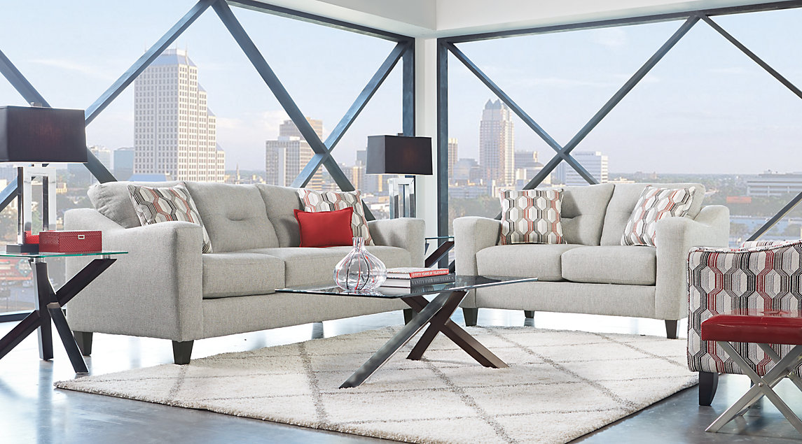 Gray sofa set, blue sky in background, white rug.